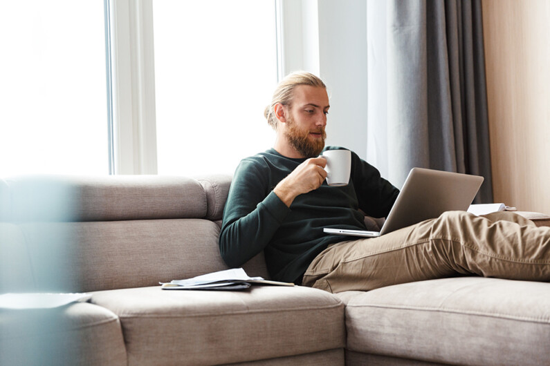 Man with beard and ponytail drining from mug whist using laptop